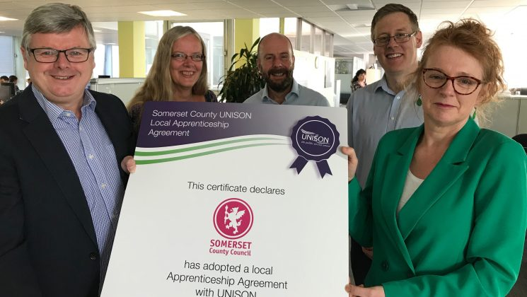 Somerset County Council Chief Exec and union officials hold A1 sized certificate confirming the council's commitment to a local apprenticeship agreement