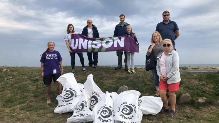 UNISON members take part in beach clean in Devon. Several members stand on a beach holding a UNISON flag showing the rubbish they collected.