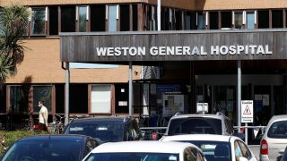 The main entrance to Weston General Hospital in Weston Super Mare. Person seen in the background wearing a face mask during the COVID-19 pandemic.
